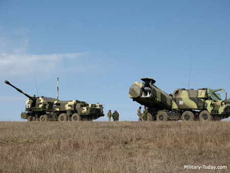 """Xe pháo tự hành 130mm tổ hợp Bereg E (trái) """"sánh vai"""" xe mang ống phóng tổ hợp tên lửa bờ 4K51 Rubezh."""