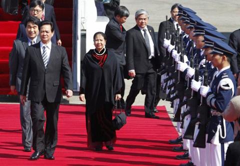 Thủ tướng và Phu nhân bước trên thảm đỏ để duyệt đội danh dự ở sân bay Seongnam. Ảnh: AFP