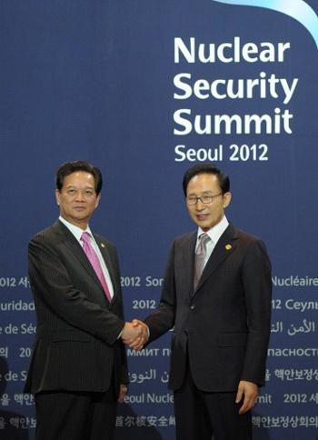 Tổng thống Hàn Quốc Lee Myung-bak thân mật bắt tay Thủ tướng Nguyễn Tấn Dũng tại buổi lễ chào đón tại Trung tâm Coex ở thủ đô Seoul, trước thềm Hội nghị Thượng đỉnh An ninh Hạt nhân lần thứ hai. Ảnh: AFP