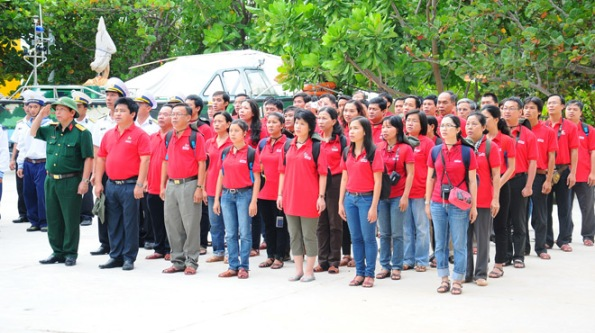 """Thành viên chuyến tàu """"Góp đá xây Trường Sa"""" chào cờ ở đảo Sơn Ca - Ảnh: T.T.D."""