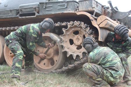 Khi lên xe các chiến sĩ là những pháo thủ, lái xe, nạp đạn giỏi. Khi xe hỏng, các anh là thợ kỹ thuật lành nghề. Trong ảnh: một kíp lái tăng sửa chữa dã chiến.