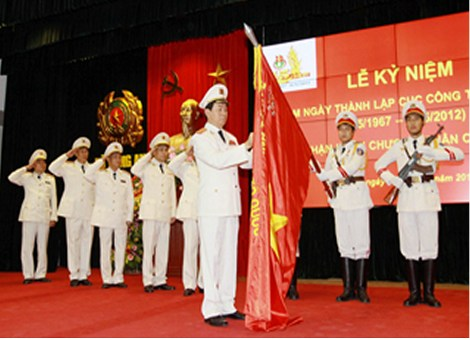 Bộ trưởng Bộ Công an Trần Đại Quang gắn Huân chương Quân công hạng Nhất lên cờ truyền thống của Cục Công tác Chính trị