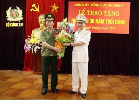 Thượng tướng Trần Đại Quang, Ủy viên Bộ Chính trị, Bí thư Đảng ủy Công an Trung ương, Bộ trưởng Bộ Công an tặng hoa chúc mừng Trung tướng Tô Lâm, Ủy viên Trung ương Đảng, Thứ trưởng Bộ Công an được tặng Huy hiệu 30 năm tuổi Đảng.