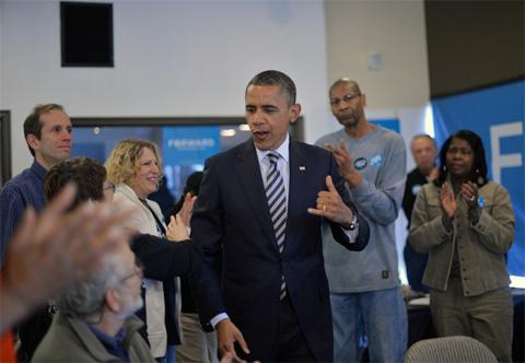 Tổng thống Barack Obama nói chuyện với các tình nguyện viên khi ông tới thăm một văn phòng vận động tranh cử tại Chicago, bang Illinois. Ảnh: AFP