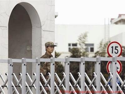 Một binh sĩ Trung Quốc đứng gác trước cổng của đơn vị 61398